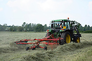 Photograph showing farmer driving tractor with tedder attached turning cut hay during the summer.  This process assists with the drying of the grass to make hay prior to baling.