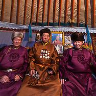 Mongolia. portrait in Adia family with traditional mongol dress, the Del.  with their medals. in the yurt area of the capital , grand father, grand mother and sohn  Ulan Baatar -  / portrait de La famille Adia, couverte de madaille. habille du vetement traditionel le Del,  dans le quartier de yourte de la capitale, les grands parents avec enfants et petis enfants  Oulan Bator - Mongolie