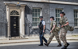 © Licensed to London News Pictures. 24/05/2017. London, UK. Armed soldiers walk past Number 10 Downing Street after being on guard duty at the gates. The terrorism threat level has been raised to critical and Operation Temperer has been deployed. 5,000 troops are taking over patrol duties under police command. Photo credit: Peter Macdiarmid/LNP