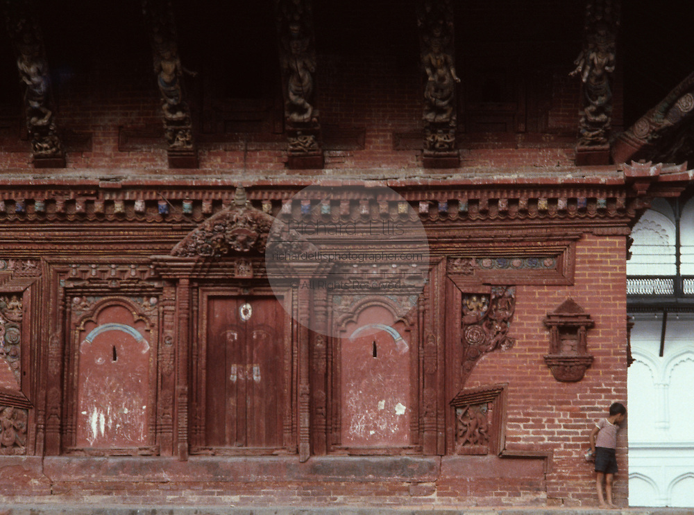 A child plays hide and go seek around a temple in Durbar Square, Kathmandu, Nepal