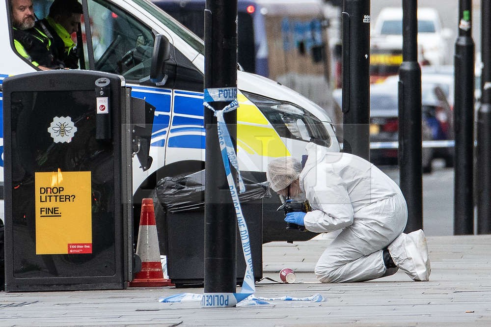 © Licensed to London News Pictures. 11/10/2019. Manchester, UK. Forensic scenes of crime examiners photograph a Costa coffee cup taken from a bin on Exchange Square at the foot of the steps to the Arndale Centre . Terrorism Police are investigating after four people were stabbed during a single attack at the Arndale Centre in Manchester City Centre . Photo credit: Joel Goodman/LNP