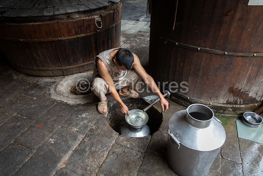 A worker opens a tap to let distilled alcohol flow out of a steam vat at a baijiu production facility that is part of the Shuijingfang museum, operated by Sichuan Swellfun Co., a unit of Diageo Plc in Chengdu, China, on Tuesday, Sept. 20, 2016. With less than 1 percent of baijiu, or white liquor, consumed abroad, Chinese distillers want to transform the fiery Chinese grain liquor into the new tequila for Americans and Europeans.
