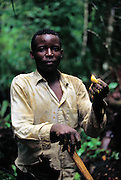 James Dyekwaso, 23, with a prime example of a masinya, or palm grub (the larvae of the Capricorn beetle), that has just been extracted from the fallen wood of a dead palm tree. Ssese Islands, Lake Victoria, Uganda. (Man Eating Bugs page 144)