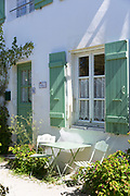 Typical quaint house with shutters traditional architecture, painted in light green at Les Portes en Re, Ile de Re, France