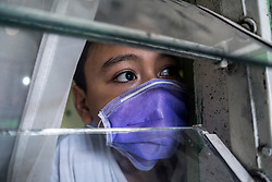 April 1, 2020, Makassar, South Sulawesi, Indonesia: A boy wearing a mask is peering in the window of his house and can't go out to play on the streets in Makassar City, South Sulawesi Province, Indonesia. The Indonesian government has asked all people who do not have important necessities to remain in their homes to prevent the spread of Covid-19. More than 1,500 patients tested positive for Covid-19 in Indonesia with more than 136 people declared dead. (Credit Image: © Herwin Bahar/ZUMA Wire)
