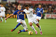 Swansea city's Jefferson Montero ® is tackled by Leicester's Ritchie De Laet.  Barclays Premier league match, Swansea city v Leicester city at the Liberty stadium in Swansea, South Wales on Saturday 25th October 2014<br /> pic by Andrew Orchard, Andrew Orchard sports photography.