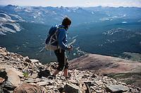 Female hiker descends rocky slopes of Mt. Dana (13,053 ft), Yosemite national park, California, USA