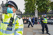 Police stand by Topless Climate activists who locked themselves against the railings of the Houses of Parliament, during an Extinction Rebellion (XR) protest, in London on Thursday, Sept. 10, 2020. Environmental nonviolent activists group Extinction Rebellion enters its 10th and final day of continuous ten days protests to disrupt political institutions throughout peaceful actions swarming central London into a standoff, demanding that central government obeys and delivers Climate Emergency bill. (VXP Photo/ Vudi Xhymshiti)