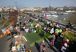 © Licensed to London News Pictures. 15/04/2019. London, UK. Children sit on a green area as Extinction Rebellion members block Waterloo Bridge during a day of coordinated actions and demonstrations  throughout London and other UK cities to highlight global climate change. Photo credit: Peter Macdiarmid/LNP