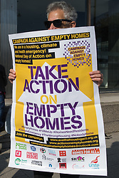 London, UK. 9th October, 2021. A housing campaigner protests outside the empty Millbank Tower as part of a national Empty Homes Day of Action. The protest was organised by groups including Action on Empty Homes, Radical Housing Network and Axe the Housing Act following the approval by Westminster Council and the Mayor of London of plans to redevelop Millbank Tower with no affordable homes as 207 luxury flats, a 150-bedroom 5-star hotel and a cultural centre.