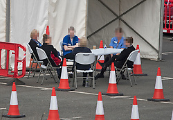 **EDITORS NOTE: Faces pixelated to hide identity**<br /> © Licensed to London News Pictures. 27/04/2020. Watford, UK. Medical staff sat at a table with nothing to do, at a COVID-19 testing centre at Watford General Hospital in Hertfordshire shortly after 10:00am. British Prime Minister Boris Johnson has warned the public against relaxing lockdown precautions too soon. Photo credit: Ben Cawthra/LNP