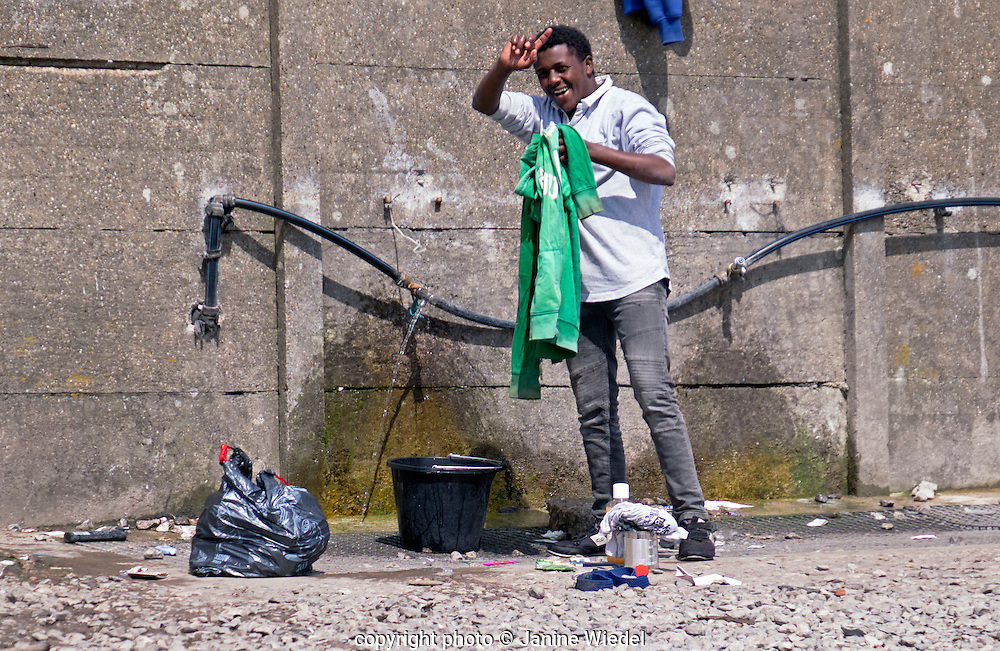 Man wahing  in The Calais Jungle Refugee and Migrant Camp in France