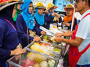 18 AUGUST 2013 - BANGKOK, THAILAND: Migrant construction workers from Myanmar (Burma) buy fruit from a Thai fruit vendor on Sukhumvit Soi 16 in Bangkok. They are working a construction site building a new hotel. Bangkok is experiencing a construction boom that is reshaping the city skyline. Most of the construction workers are from the Isan region of northeastern Thailand, but many also come from Laos and Myanmar to work in the Thai construction trade because they can make more than twice as much in Thailand and they can in their countries of origin.       PHOTO BY JACK KURTZ