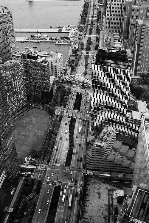 """Back in 2013 while on assignment photographing the first fully outfitted floor of One World Trade Center I snapped a few images of the city. While the view out over the city was stunning I was much more interested in all of the activity happening just around the """"neighborhood."""" Being able to look down from such a height revealed a world of patterns, shapes, and people scurrying about. It was fascinating.  <br /> It was a dreary overcast day as well and while that may not offer the everyday pedestrian much with regards to experience, photographers love it! It works to considerably benefit the black and white photographer as it gives us large, soft shadows, and a flat negative or file to work with. Black and white images made on an overcast day tend to sound like a somber piece by Mendelssohn. There is a richness and romantic quality which the clouds bestow upon the world."""
