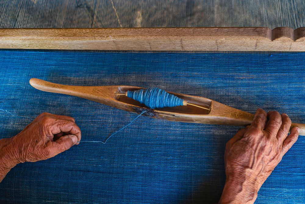 A woman's hands threading woollen yarn dyed with indigo onto a bobbin on a traditional loom, Indigo Dyeing Factory, Sakhon Nokhon, Thailand