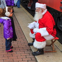Strasburg, PA / USA - December 19, 2015: A young girl has a word with Santa before posing for pictures at the Strasburg Rail Road.