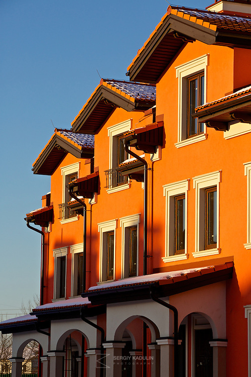 """Architectural details of residential real estate development project """"Italian Village"""" in Kyiv, Ukraine. Exterior view of townhouses with red walls in the sunset sunlight."""
