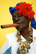Cuba, Havana. Portrait of a typical Cuban woman smoking a cigar.