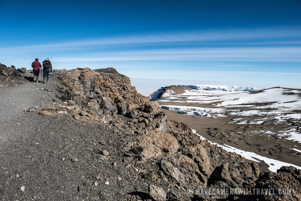 Two hikers approach Uhuru Peak on the summit of Mt Kilimanjaro. The sign marking the summit can be seen in the distance with a group of hikers. At right are some of the permanent glaciers on the summit.
