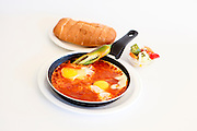 Shakshouka is a Tunisian and Israeli dish made of cooked tomatoes, peppers, spices and eggs. It is cooked on low flame starting with the vegetables and spices; once these are cooked, the egg is added.