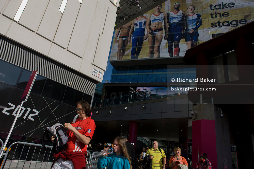 A spectator arrives with a ticket in mouth at the Westfield Stratford shopping mall near the entrance of the Olympic Park during the London 2012 Olympics. .Situated on the fringe of the Olympic park, Westfield is Europe's largest urban shopping centre. The £1.45bn complex houses more than 300 shops, 70 restaurants, a 14-screen cinema, three hotels, a bowling alley and the UK's largest casino. It will provide the main access to the Olympic park for the 2012 Games and a central 'street' gives 75% of Olympic visitors access to the main stadium so retail space and so far 95% of the centre has been let. It is claimed that up to 8,500 permanent jobs will be created by the retail sector.