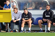 AFC Wimbledon manager Neal Ardley, AFC Wimbledon first team coach Simon Bassey and AFC Wimbledon goalkeeping coach Ashley Bayes watching the ga,e during the EFL Sky Bet League 1 match between AFC Wimbledon and Portsmouth at the Cherry Red Records Stadium, Kingston, England on 13 October 2018.