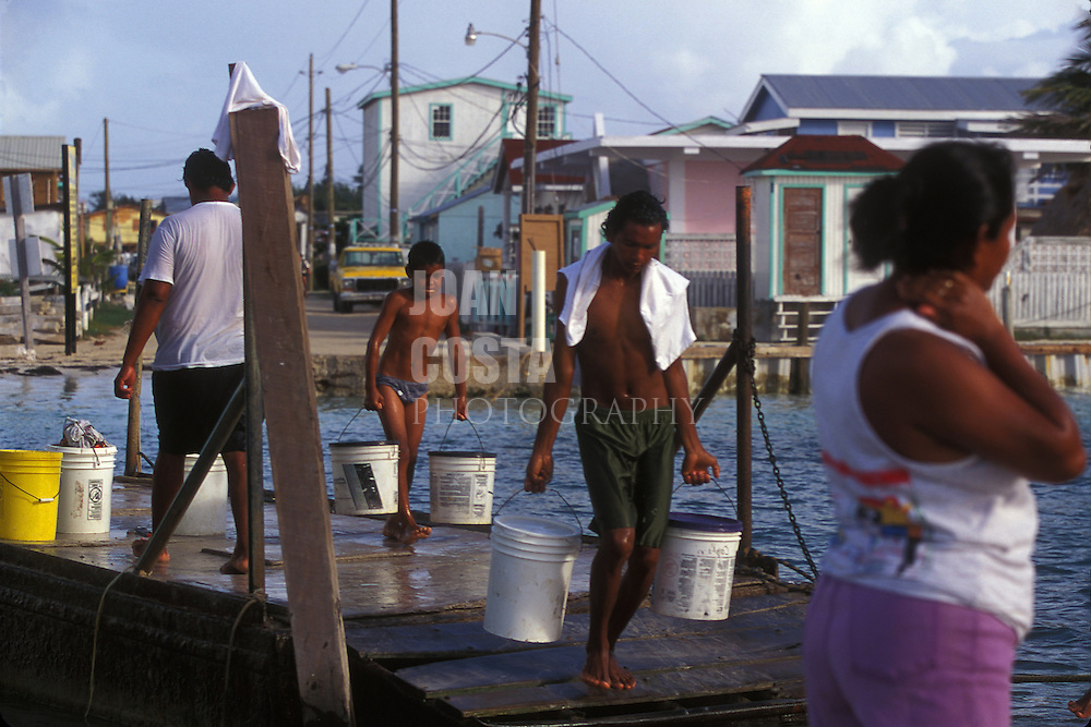 BELIZE / San Pedro / People carrying water buckets...© JOAN COSTA