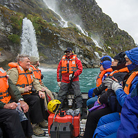 Tourists ride in a zodiac raft below a waterfall pouring into Seno Chico, a fjord in Alberto de Agostini National Park, Tierra del Fuego, Chile.