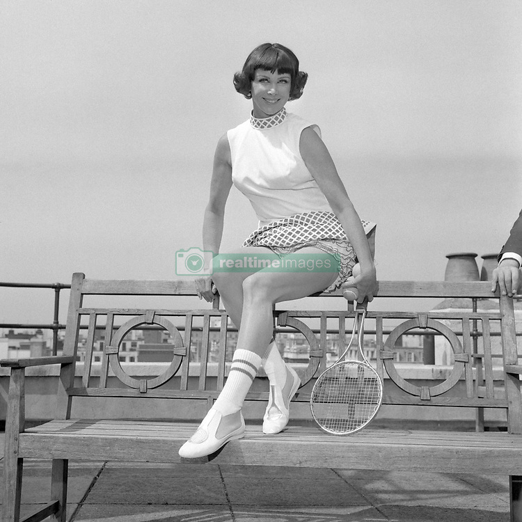 'Gorgeous' Gussie Moran, the girl who started Wimbledon by wearing lace panties on court in 1949, is back in London to see the first Open Wimbledon. She is pictured on the roof of Simpson's department store in Piccadilly, London, where she is to give a series of tennis demonstrations from tomorrow to Saturday. The tennis dress she is wearing has a long torso line and a ballerina skirt in guipure made to match the stringing of a tennis racket and to blend in with this year's outer-space blue.