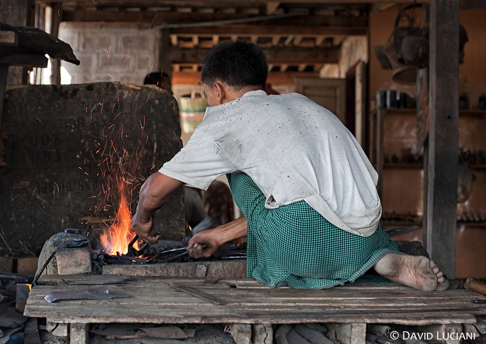 A man prepares a piece of iron to be forged.