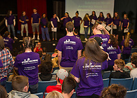 Laconia High School's assembly for Stand Up Laconia provides information on substance abuse with the number of resulting deaths on the front of their purple shirts.   (Karen Bobotas/for the Laconia Daily Sun)