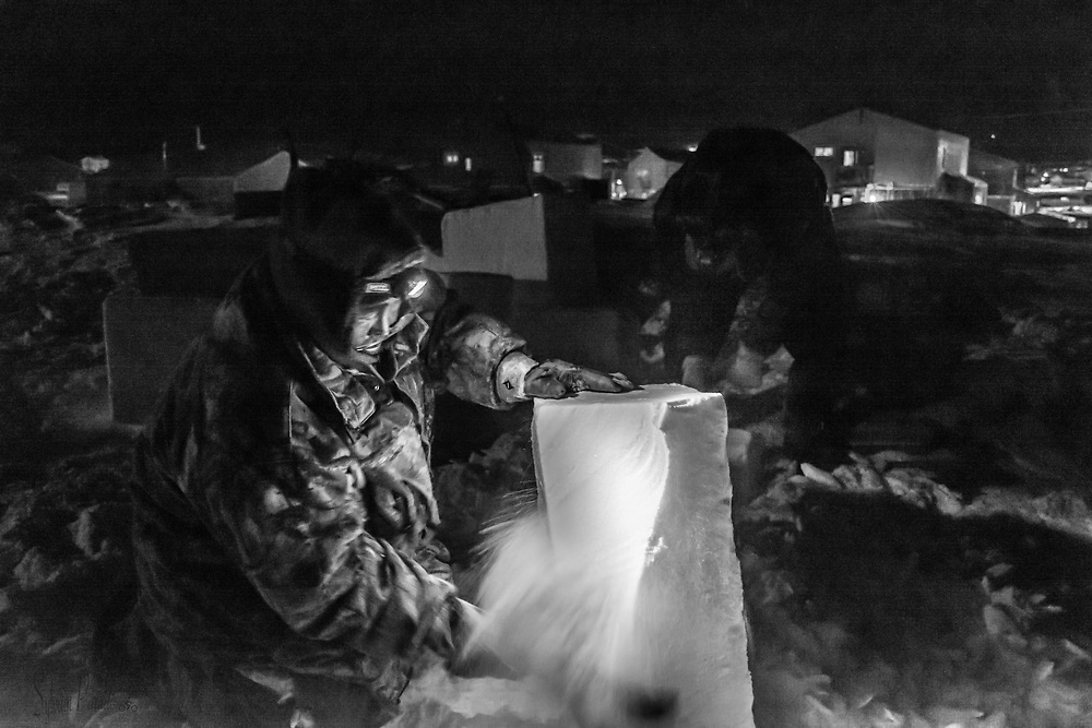 This man is was cutting and chopping big blocks of hard packed snow, at night. He was clearing his sled. A qamituk in inuktitut.