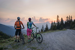 Rear view of young couple of mountain bikers standing in the alpine landscape and looking at view during sunset, Zillertal, Tyrol, Austria