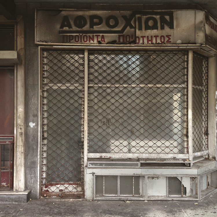 """A closed down shop in Plateia Vathi, Athens that used to sell mattresses and pillows. The sign reads """"Afrohion"""""""