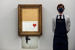 """© Licensed to London News Pictures. 03/09/2021. LONDON, UK.  **UNDER EMBARGO UNTIL FRIDAY 3 SEPTEMBER 2021, 12PM BST** A technician presents """"Love Is in the Bin"""" by Banksy at a preview at Sotheby's.  The painting, originally known as """"Girl with Balloon"""", was famously shredded by the artist in Sotheby's London auction room in 2018 after being sold for £1,042,000.  The resulting artwork was later renamed """"Love Is in the Bin"""" and will be offered for sale in Sotheby's contemporary art evening auction on October 14 with an estimate of £4-6 million.  Photo credit: Stephen Chung/LNP"""
