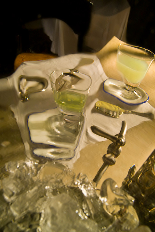 """Clarity's sister. The vertical view of an absinthe table from inside an absinthe fountain. The wavy glass of the bowl helps to convey the mythical hallucinogenic atmosphere of the green hour. The absinthe """"ritual"""" requires the use of unique accoutrements as seen on the table. The absinthe fountain with ice in the bottom and one spicket at the bottom is central as it provides ice cold dripping water to louche absinthe which is the proper way to drink this green cocktail. Two glasses of louched green opaque absinthe on absinthe glass saucer. Silver absinthe spoon on white napkin. Reflections of the  Belle Epoque, """"The Beautiful Era""""."""
