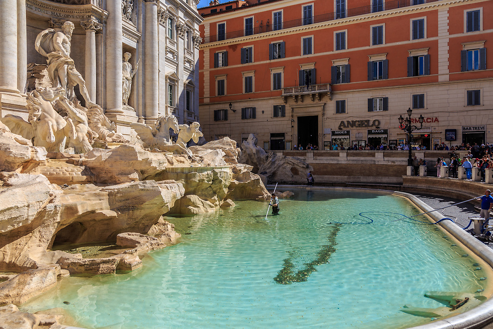 Coin collecting in Fontana di Trevi in Rome, Italy. Tradition holds that visitors can assure their return by tossing a coin over their left shoulder into the water. At least for now, Caritas Rome uses the tourists' coins to provide food and shelter to the city's poor and needy.