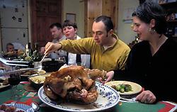 Family sitting down to eat Christmas dinner - turkey & all trimings; UK