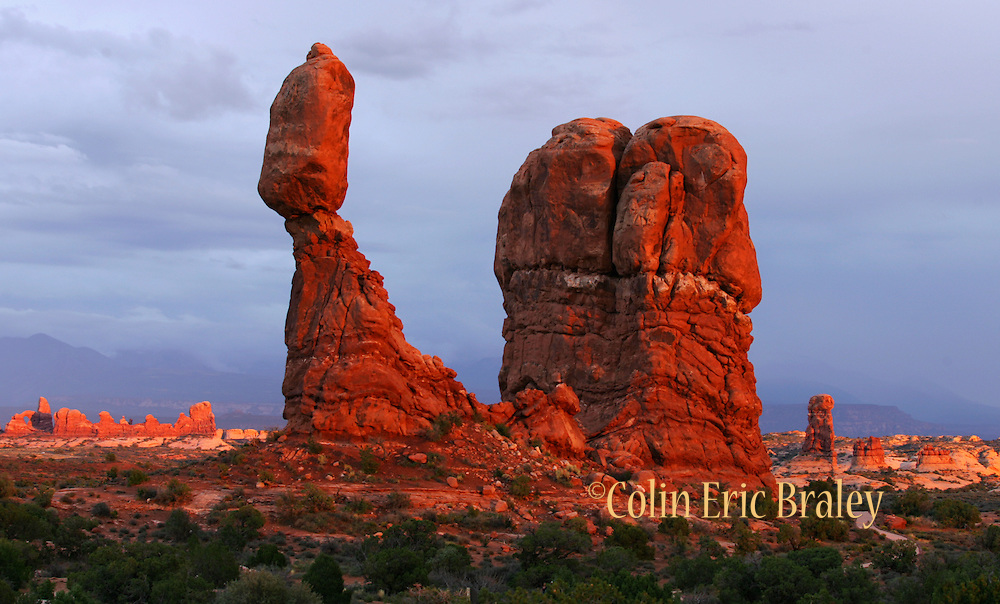 Arches National Park glows red during a sunset as a passing storm darkens the sky. Balanced Rock is seen in the forground. 9/4/06