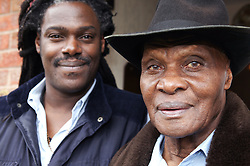 Portrait of an elderly man standing in front of a younger man smiling,