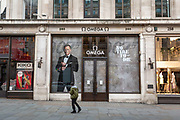 A man walks past a promotion for the new James Bond fIlm, A Time To Die, at the closed Omega store on Regent Street in the early evening in London on March 27th, 2020. The release date for the film has been postponed from 10th April to 25th of November due to the Coronavirus crisis.