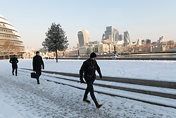 © Licensed to London News Pictures. 28/02/2018. London, UK. Commuters walk to work on the south bank in front of the City of London through snow in London this morning. London has experienced heavy snow fall and freezing weather overnight. Photo credit: Vickie Flores/LNP