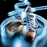 A creative, light painted product shot of a pair of Adidas training shoes.