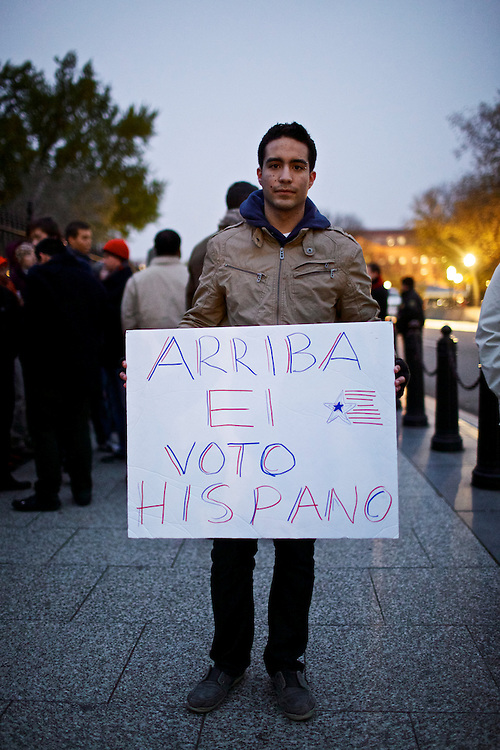 """Miguel Tavera, 18, shows his continued support of President Barack Obama on Wednesday, Nov. 7, 2012 in Washington, D.C. Tavera is originally from Broward County Florida and voted first time this year by absentee ballot. He and fellow students from George Washington University stood outside of the White House to catch a glimpse of the President as he returned to Washington from Chicago on Wednesday evening. Tavera said his sign indirectly translates """"power to the Hispanic vote."""""""