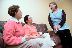 Carer talking older woman and her daughter at home,