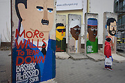 "World dictators (incl Syrian President Bashir al-Assad) adorn old sections of the old Berlin Wall opposite the former Checkpoint Charlie, the former border between Communist East and West Berlin during the Cold War. The Berlin Wall was a barrier constructed by the German Democratic Republic (GDR, East Germany) starting on 13 August 1961, that completely cut off (by land) West Berlin from surrounding East Germany and from East Berlin. The Eastern Bloc claimed that the wall was erected to protect its population from fascist elements conspiring to prevent the ""will of the people"" in building a socialist state in East Germany. In practice, the Wall served to prevent the massive emigration and defection that marked Germany and the communist Eastern Bloc during the post-World War II period."