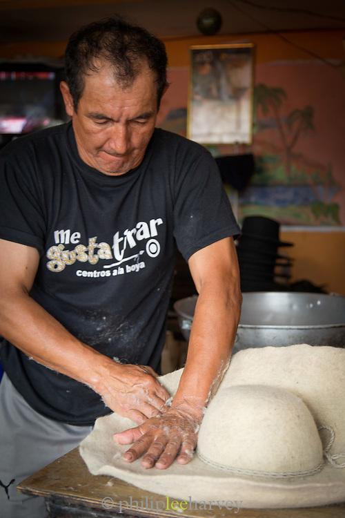 A hat maker shapes wet felt into hats, Ecuador, South America