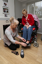 Carer putting Wheelchair user's shoes