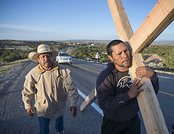 April 14, 2017 - Santa Fe, New Mexico, U.S. - JAIME GONZALES, left, and JEORGE MARTINEZ, from Santa Fe, carry a cross along Highway 503 on their way to the Santuario de Chimayo. With beautiful weather, thousands of people were making the Good Friday pilgrimage to the Northern New Mexico church. (Credit Image: © Eddie Moore/Albuquerque Journal via ZUMA Wire)