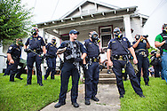 The Baton Rogue police stand on the lawn of  home  in Baton Rouge on Sunday, July 10, 2016.  6 days following the Alton Sterling shooting, the police areseted Aproximaetly 48 people had been were taken into custody by midnight Sunday,